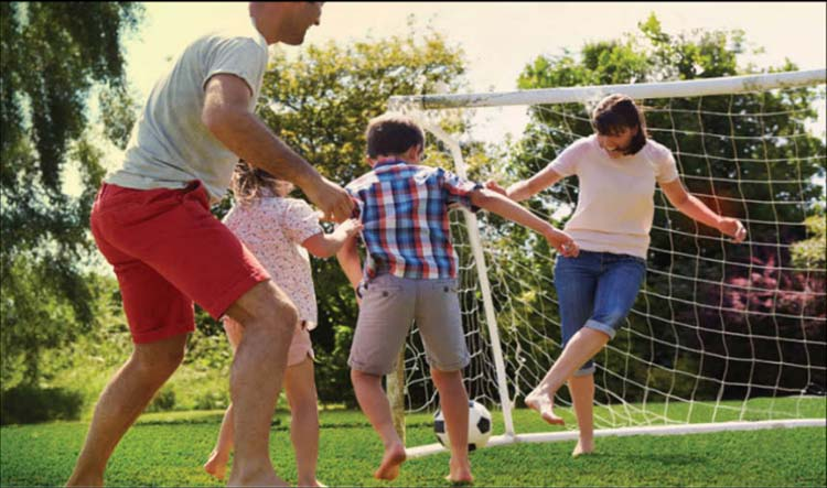 Family enjoying soccer on artificial turf