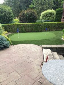 Two hole synthetic putting green for challenging up and downhill putts