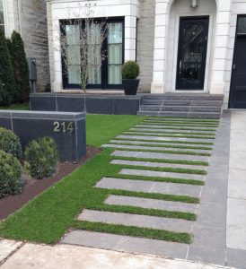 Nice walkway to front door with artificial grass between stone pavers