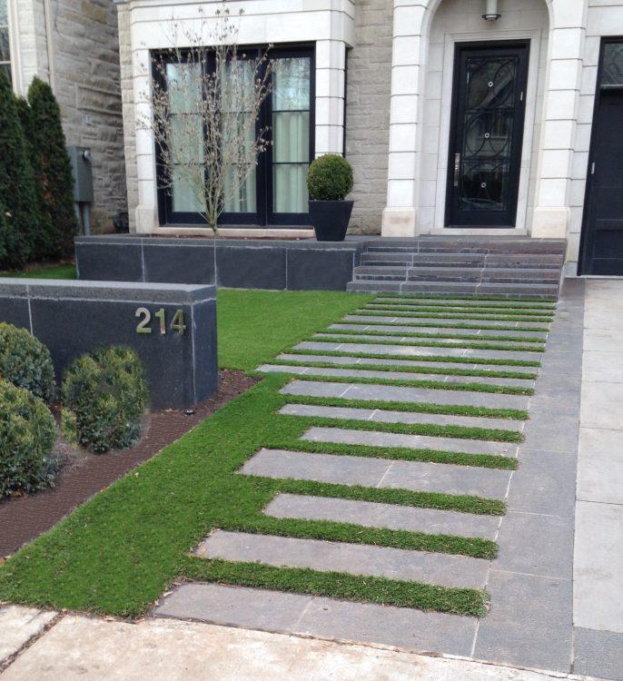 Nice walkway to front door with artificial grass between stone pavers
