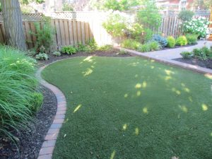 Synthetic lawn surface framed with Unilock pavers creates separation from garden