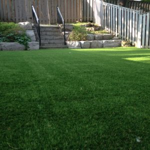 Artificial grass meets upper tier stairs and retaining wall