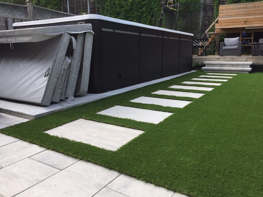 Above ground pool, flagstone path and artificial grass make for a lovely backyard