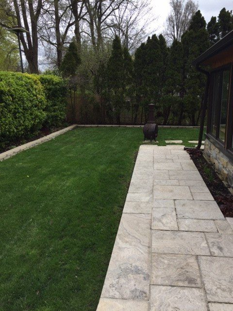 Hedging curbing patio accentuated by fake grass