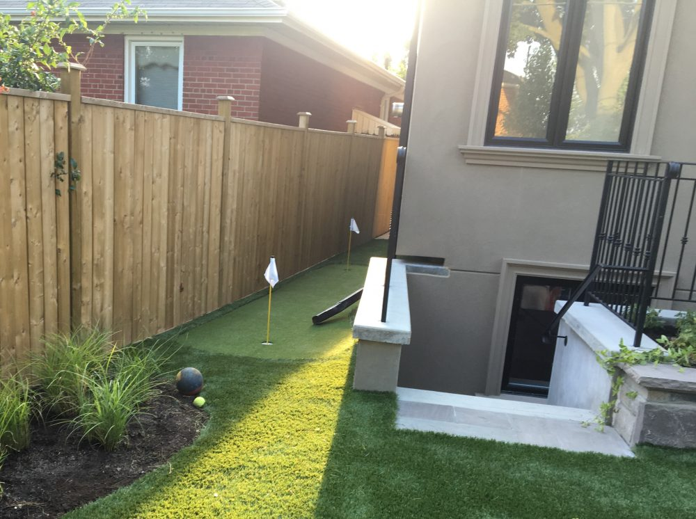 narrow synthetic golf green at side yard