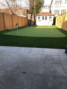 4 hole golf green in balance with fencing & white shed