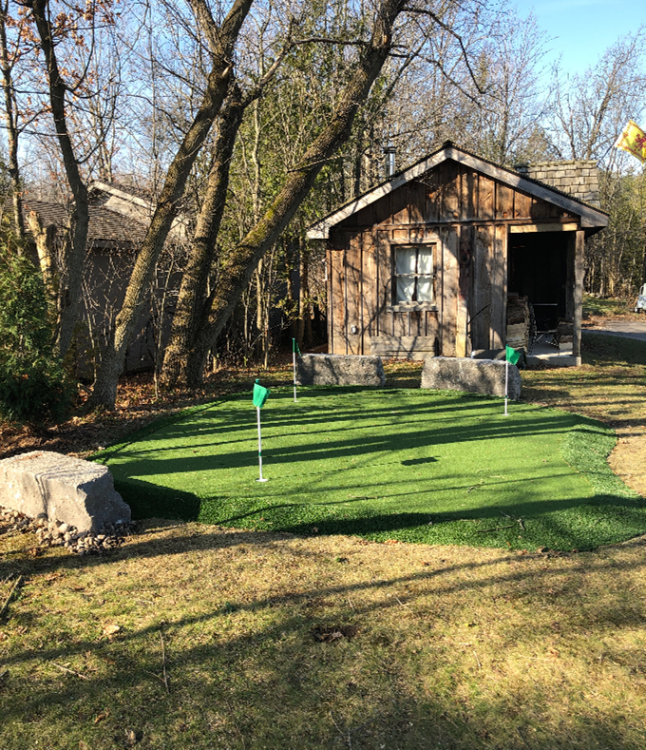 A rustic cabin with large armour stone & golf green